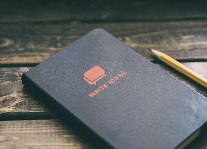 """Black notebook labeled """"Write Ideas"""" on a table next to a pencil."""