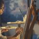 Woman sitting at easel painting art.