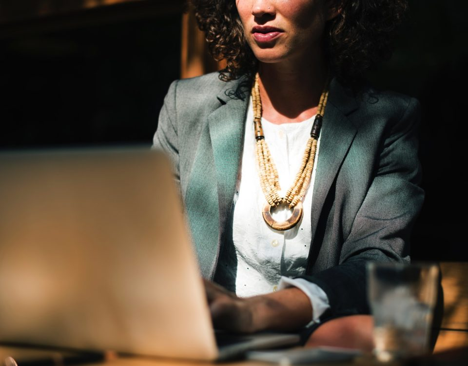 Woman sits at her computer writing a book or thesis. She is using our 4 time management strategies to write more effectively.