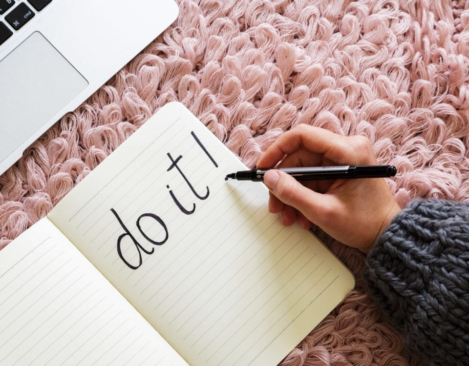 "Woman writes ""Do it!"" in a notebook in black marker."